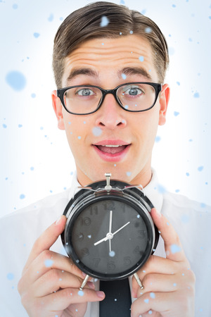 Geeky businessman holding alarm clock against snow falling photo