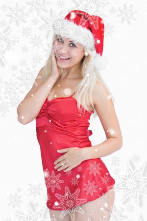 wearing santa hat: Excited woman wearing santa hat against snowflakes Stock Photo