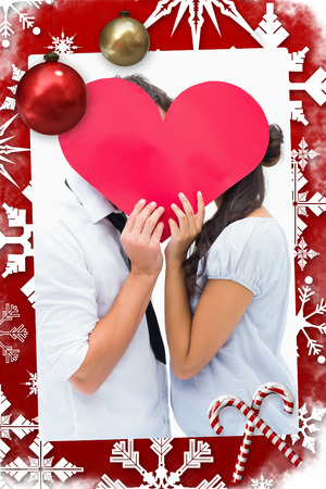 Couple covering their kiss with a heart against christmas themed page photo