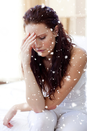 Composite image of Beautiful woman having a headache in bed with snow falling photo
