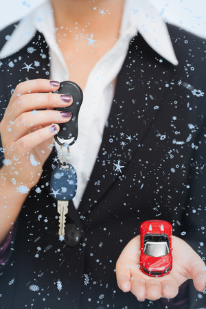 Composite image of Woman holding key and small car in her palm with snow falling photo