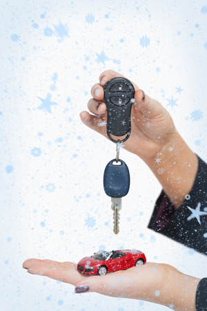 Composite image of Woman holding key and small car with snow falling photo