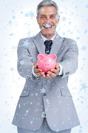 Composite image of Wide smiling businessman holding piggy bank with snow falling photo