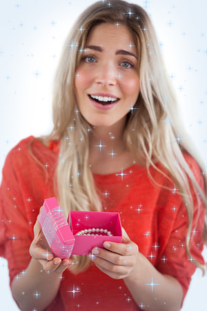 Composite image of Surprised blonde woman opening gift with twinkling stars photo