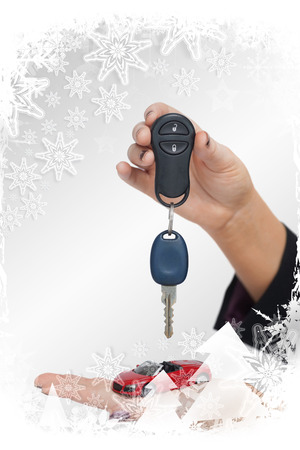 Composite image of Woman holding key and small car in a christmas frame photo