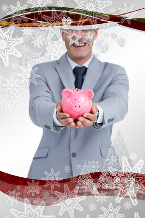 Composite image of Wide smiling businessman holding piggy bank in a christmas frame photo