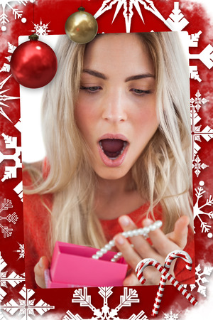Composite image of Shocked woman discovering necklace in a gift box in a christmas themed page photo