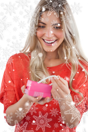 Composite image of Blonde woman discovering necklace in a gift box with snowflakes photo