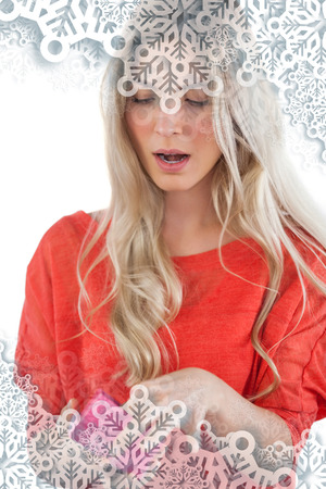 Composite image of Surprised woman opening her gift with snowflakes on silver photo