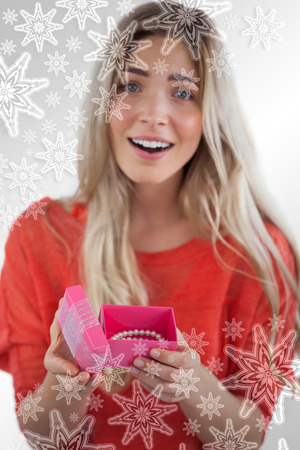 Composite image of Surprised blonde woman opening gift with snowflakes on silver photo