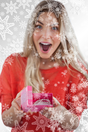 Composite image of Surprised woman discovering necklace on a box with snowflakes on silver photo