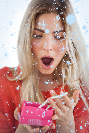 Composite image of Shocked woman discovering necklace in a gift box with snow falling photo