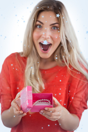 Surprised woman discovering necklace on a box with snow falling photo