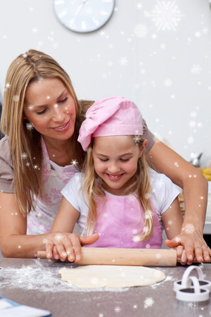 Mother and daughter baking biscuits in the kitchen with snow falling photo
