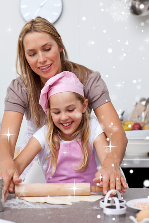 Mother and daughter baking cookies in the kitchen with snow falling photo
