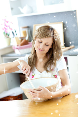 gratified: Portrait of a teen woman preparing a cake in the kitchen with snow falling