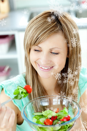 gratified: Young woman eating a salad in the kitchen with snow falling