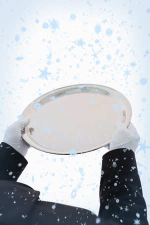 Large silver tray being held out against snow falling photo