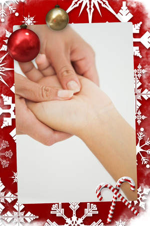 Composite image of woman receiving a hand massage in a christmas themed page photo