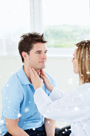 Female doctor examinating the throat of a happy patient sitting in her office with snow falling photo