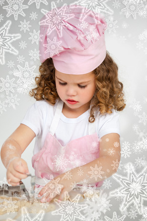 Cute little girl making biscuit at a table with snowflakes on silver photo