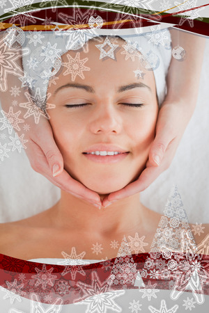 facial massage: Portrait of a smiling woman having a facial massage in a christmas frame