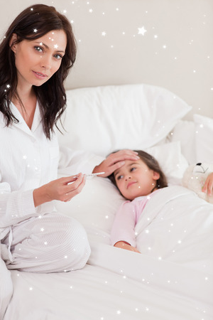 Concerned mother checking on her daughters temperature against twinkling stars photo