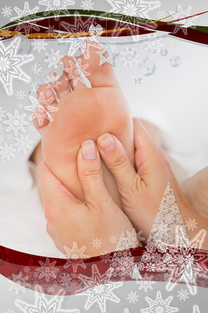 Close-up of a woman receiving foot massage against christmas frame photo