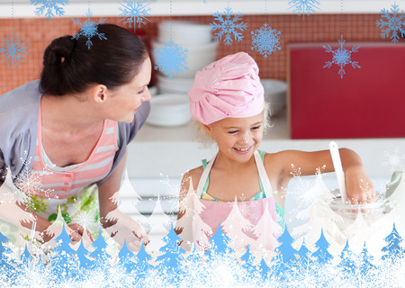 Cheerful mother and her daughter baking in a kitchen against snowflakes and fir trees photo