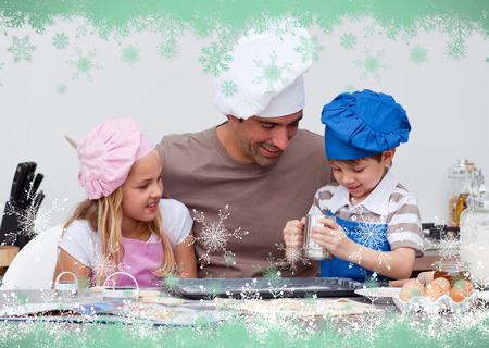 Father and children baking in the kitchen against snow flake frame in green photo