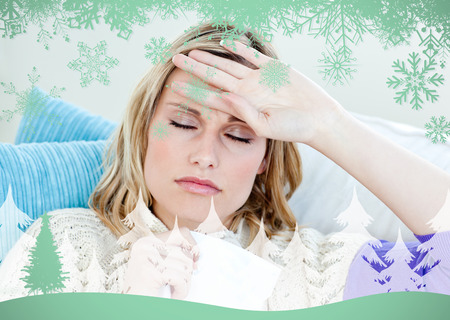 poorly: Sick woman with headache lying on the sofa in the livingroom against snowflakes and fir tree in green Stock Photo