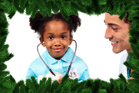 Attentive doctor playing with his patient  against fir tree branches forming frame photo