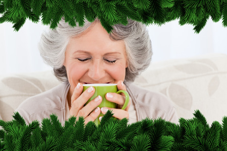 Senior drinking a cup of tea against fir tree branches forming frame photo