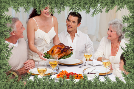 Woman showing turkey to her family for Christmas dinner against green fir branches photo