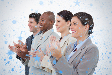 upright row: Side view of clapping sales team standing together against snow falling Stock Photo