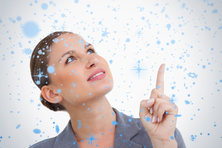 Close up of tradeswoman looking and pointing up against snow falling photo