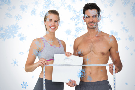 Sporty couple holding scales and measuring tape against snow falling photo