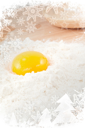 Egg yolk on white flour in a christmas frame photo