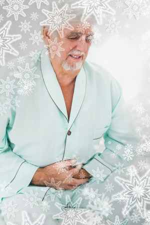 Man with pain in stomach against snowflakes on silver photo