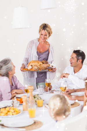Composite image of mother bringing turkey to dinner table against snow falling photo