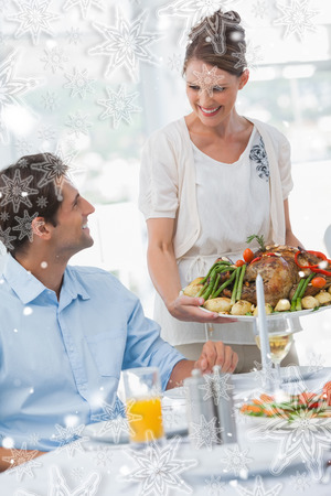 Cheerful woman presenting a roast chicken against snowflakes photo