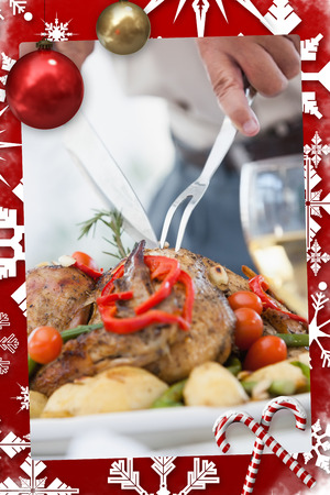 Close up of a man carving the roast chicken against christmas themed page photo