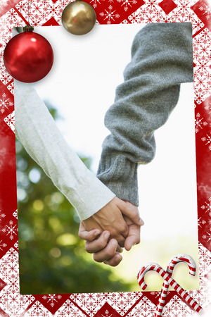 Cute couple holding hands in the park against christmas themed page photo