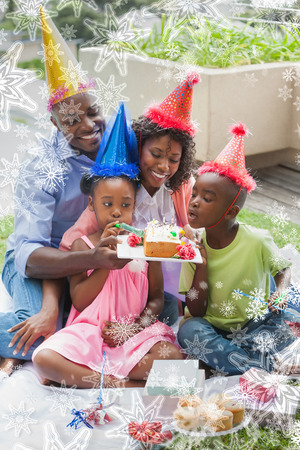 Family celebrating a birthday together in the garden against snowflakes on silver photo