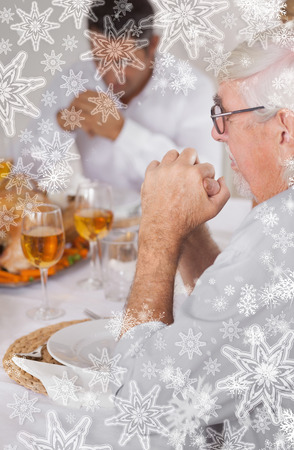 Family saying grace before eating against snowflakes on silver photo