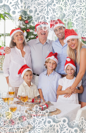 Composite image of smiling family at christmas against snowflakes on silver photo