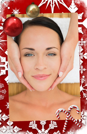 day care: Peaceful brunette enjoying a facial massage against christmas themed page Stock Photo