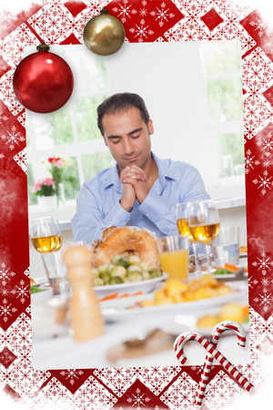 Man saying grace before dinner against christmas themed page photo