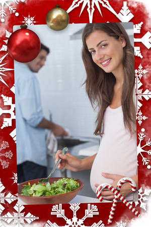 Pregnant woman preparing a salad in the kitchen against christmas themed page photo