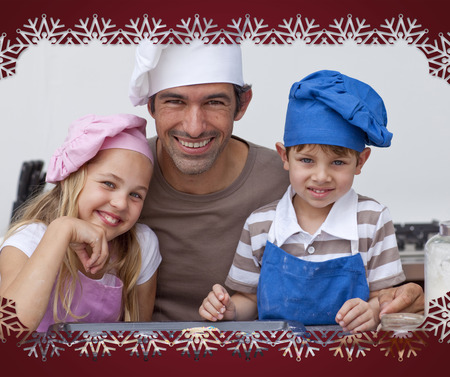 Happy father and children baking cookies together against snowflake frame photo